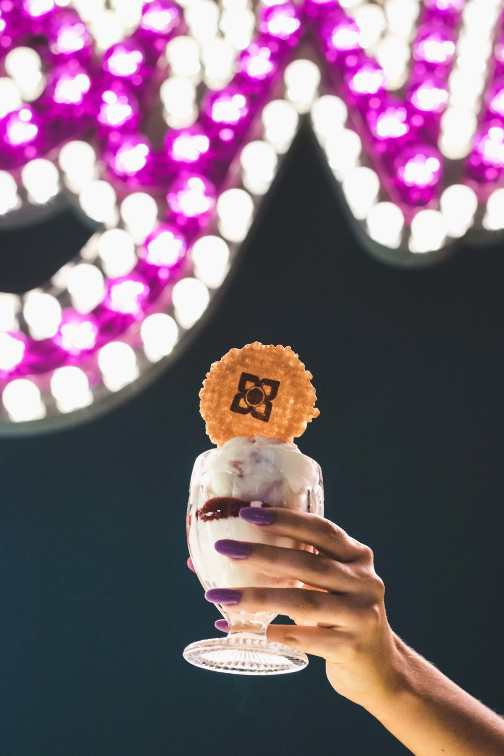 A cup of ice cream topped with a wafer in front of the Ruby Violet sign