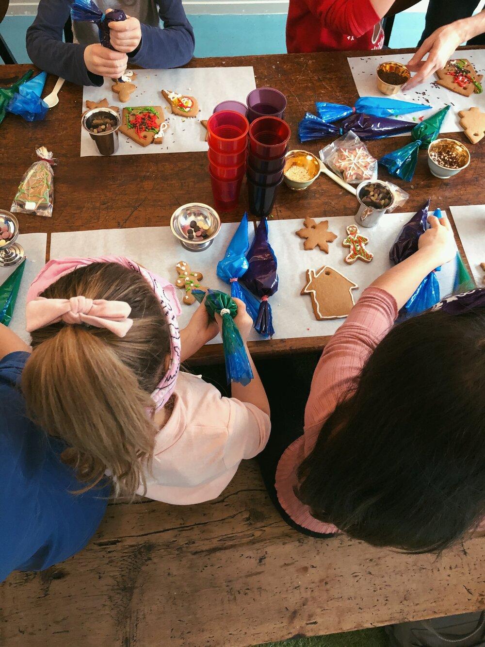 Children decorating gingerbread biscuit during a workshop
