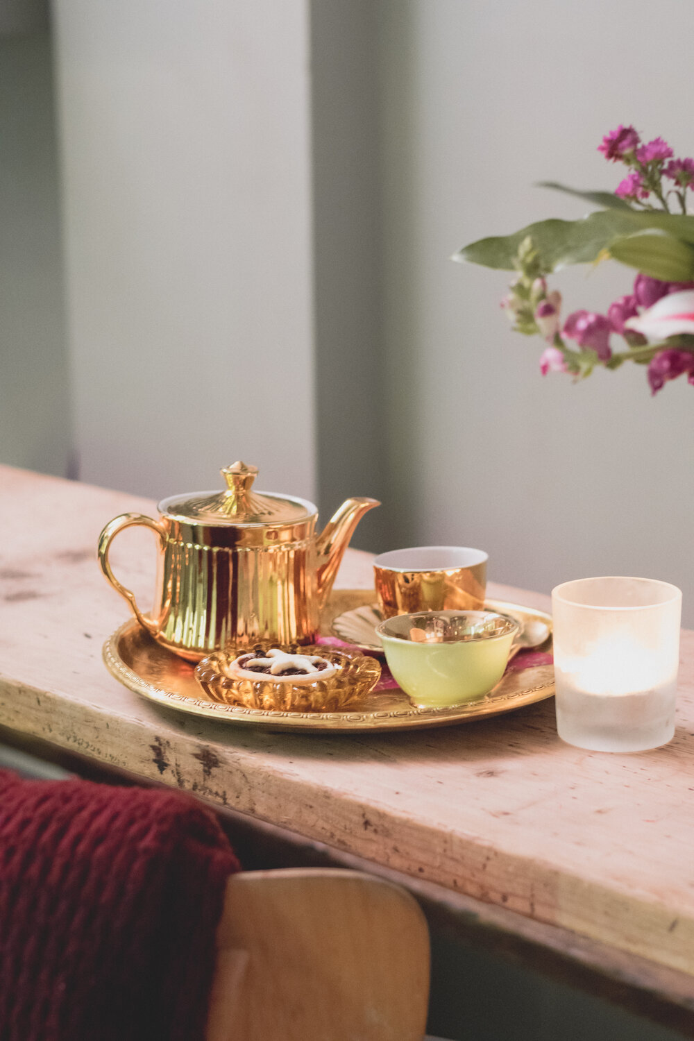 A golden teapot and cup on a tray with a homemade mince pie, scarf and candle
